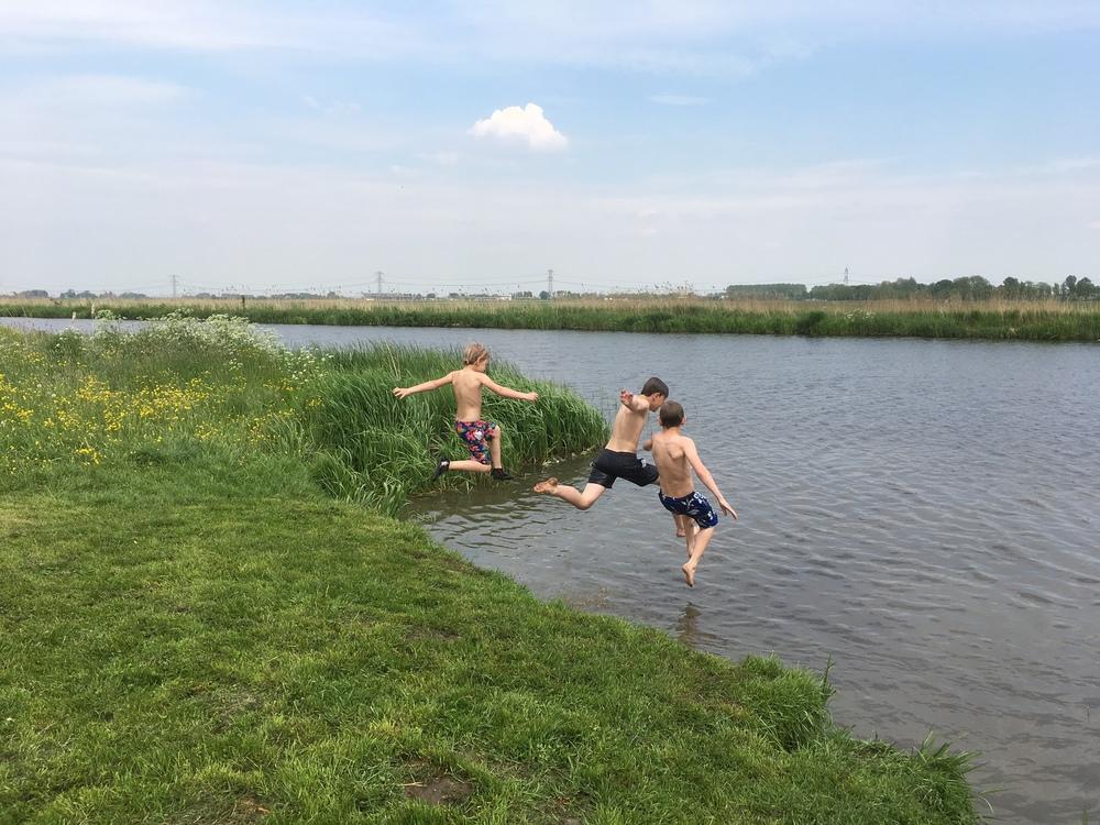Kinderen springen in het water.