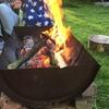 Mensen genieten naast het kampvuur in een vuurschaal.