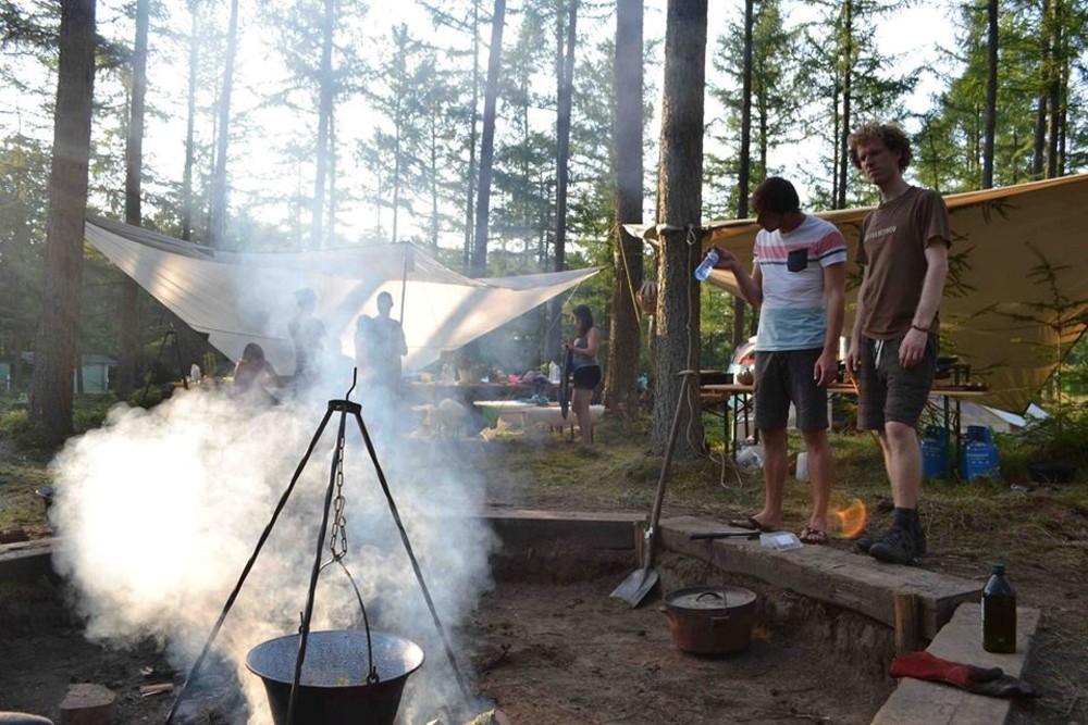 Kampvuur met een pot eten erboven op Kamp Buitendoor.