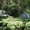 Camper en tent gebroederlijk op het veld.
