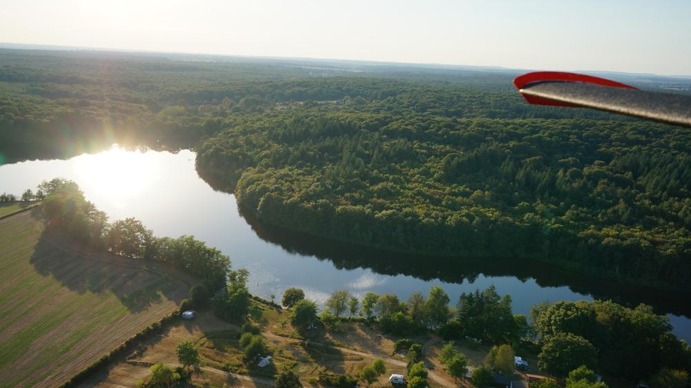 NatuurKampeerterrein Vue du Lac in vogelvlucht. Je staat midden in de natuur met bos, weiland en water om je heen.