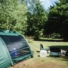 Voor de tent zitten met uitzicht op het bos.