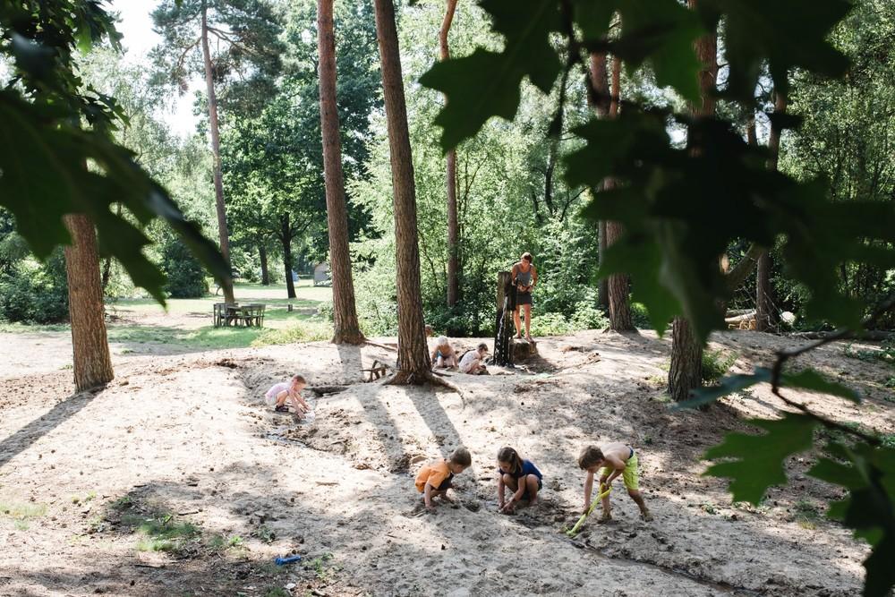 Kinderen vermaken zich met zand tussen de bomen.