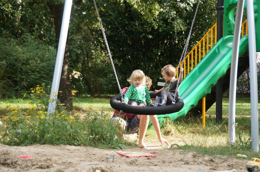 kinderen op de schommels in de speeltuin